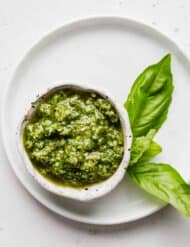 Basil pesto in a small white bowl against a white background.