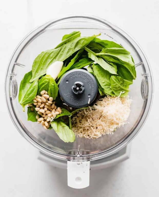 A food processor full of basil pesto ingredients.