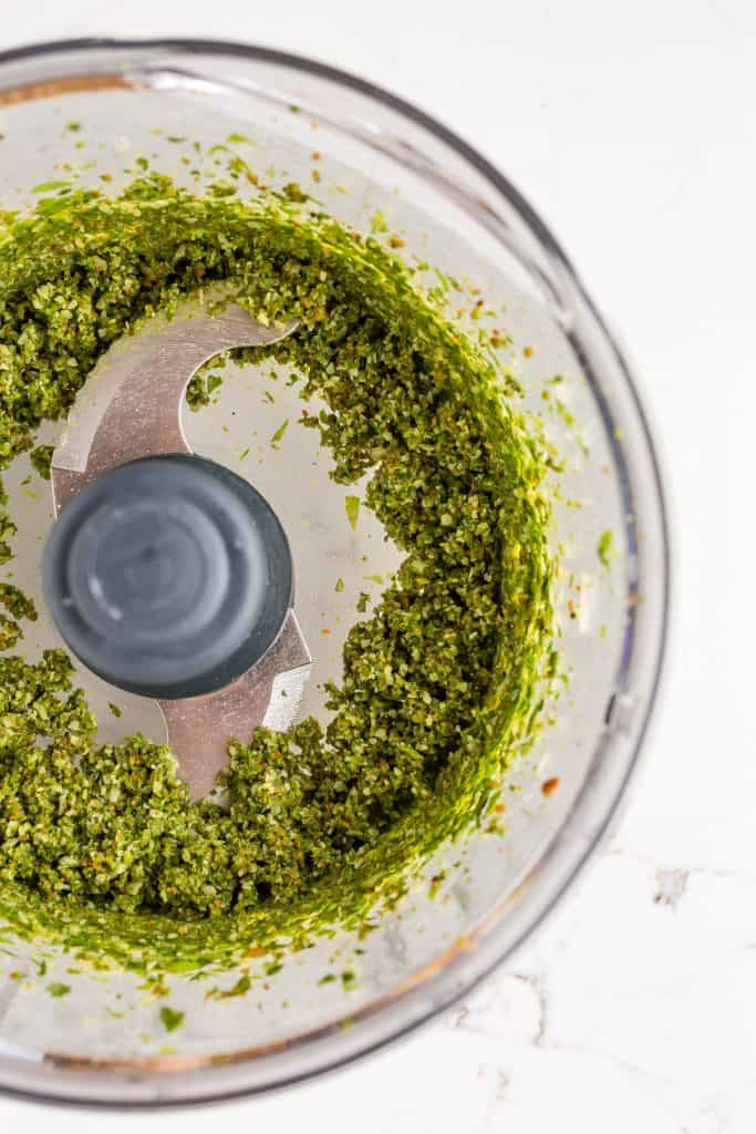 Finely chopped basil pesto ingredients, sitting in the bowl of a food processor.
