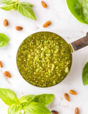 Basil pesto in a measuring cup against a white background.