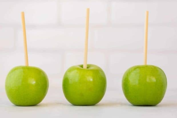 Three green apples with sticks poked into the stems.