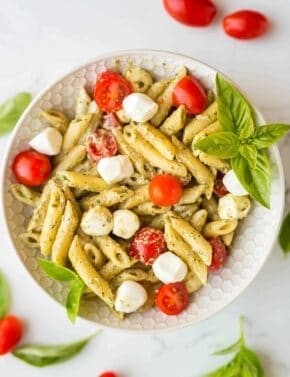 Overhead photo of a bowl of basil pesto pasta tossed with cherry tomatoes, and mozzarella balls.