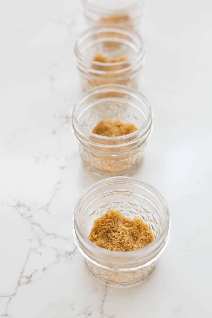 A line of four, 4 oz glass jars, each with a small dose of graham cracker crumbs lining the bottom of the jar.