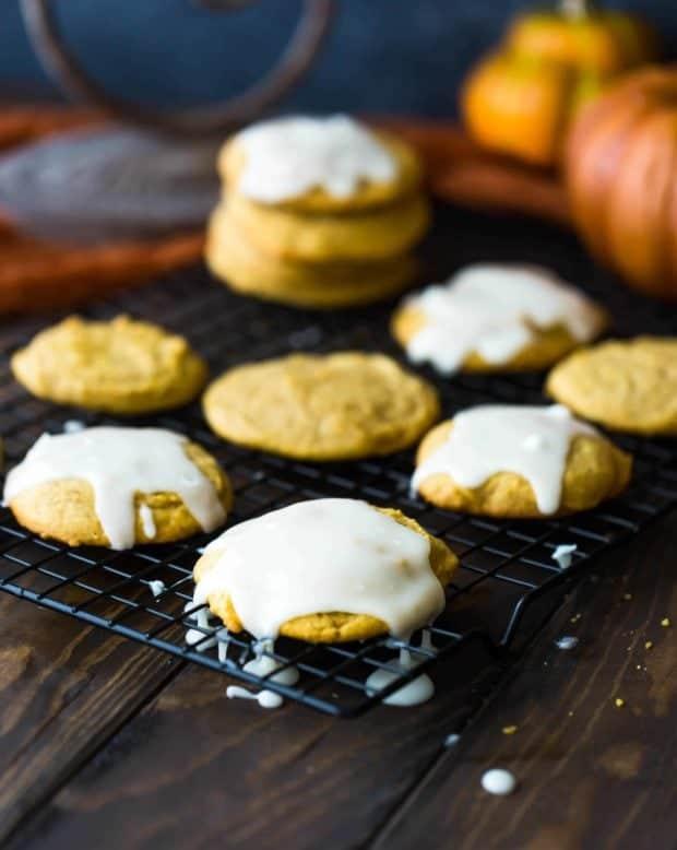 Glazed pumpkin cookies on a black cooling rack.
