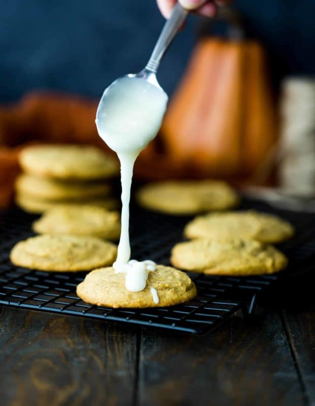 White glaze dripping off a spoon onto a pumpkin cookie.
