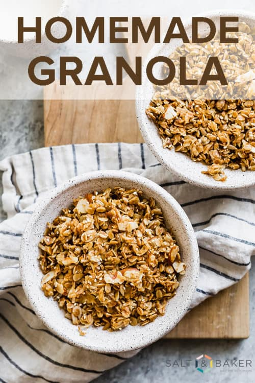 Overhead photo of two bowls full of homemade granola, sitting atop a white and navy striped linen napkin.