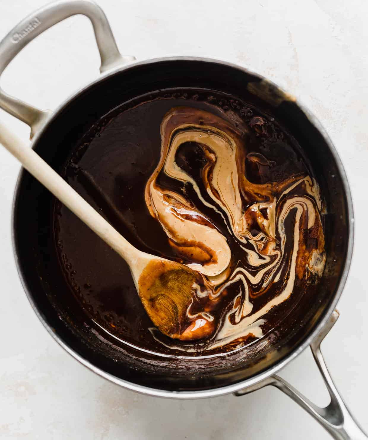 A saucepan with a peanut butter being mixed into a cocoa mixture.
