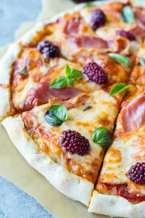 A slice of pizza topped with prosciutto, blackberries, and fresh basil.