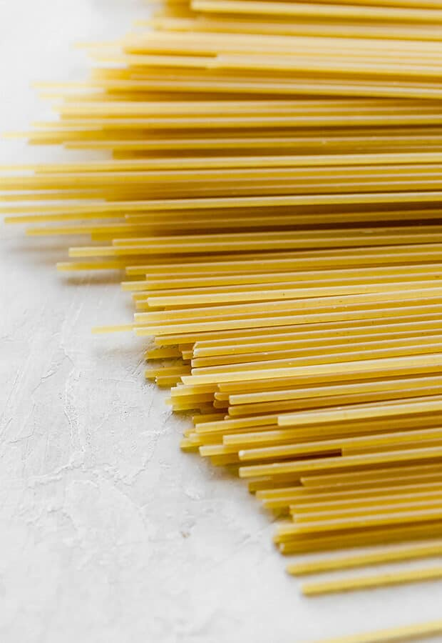 A close up photo of uncooked spaghetti pasta noodles.