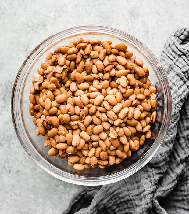 A glass bowl full of the cooked pinto beans.