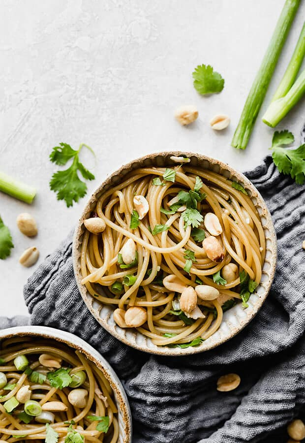 A close up photo of sesame noodles topped with peanuts.