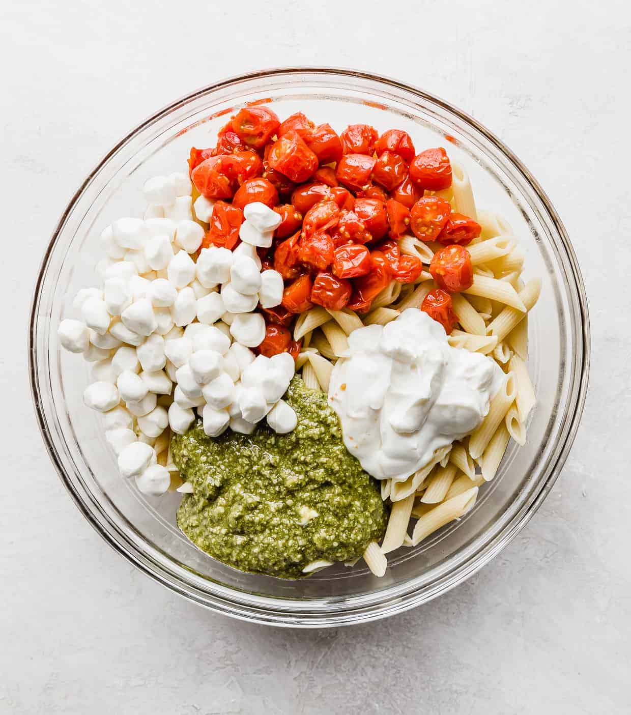 A glass bowl with grape tomatoes, mozzarella balls, sour cream, pesto, a top cooked penne noodles.