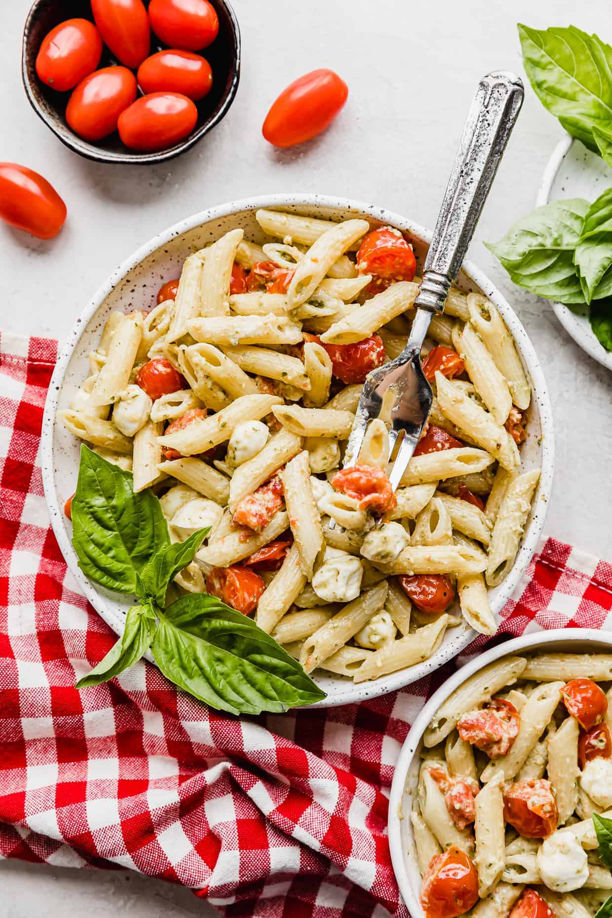A white plate with Pesto Pasta with Tomatoes and mozzarella balls.
