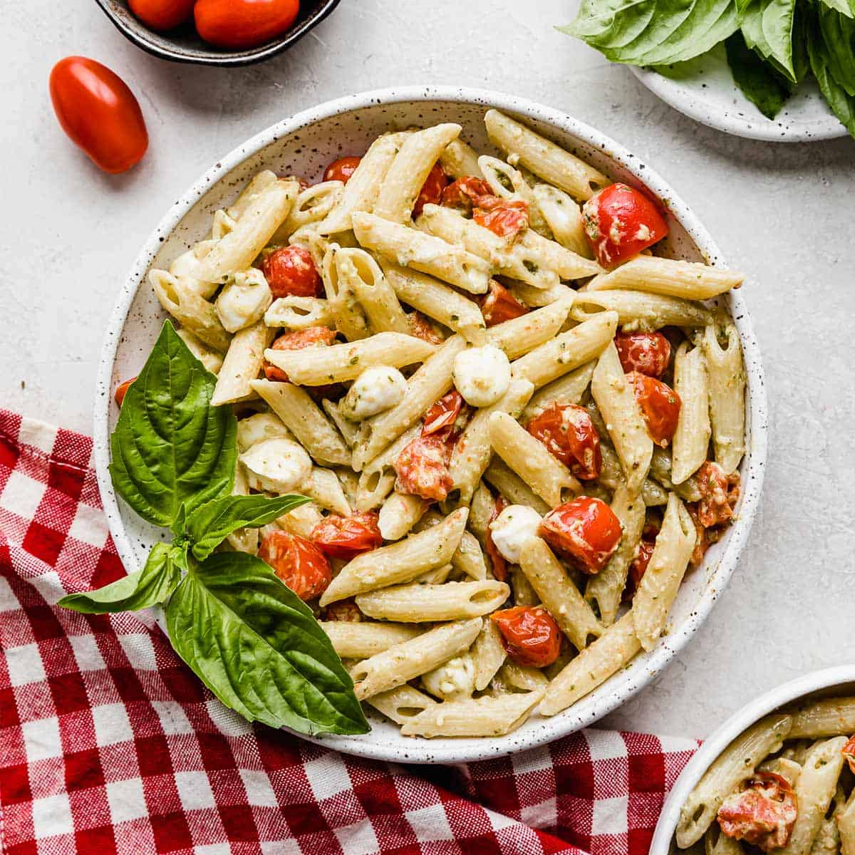 A bowl of creamy pesto pasta with tomatoes and mozzarella balls.