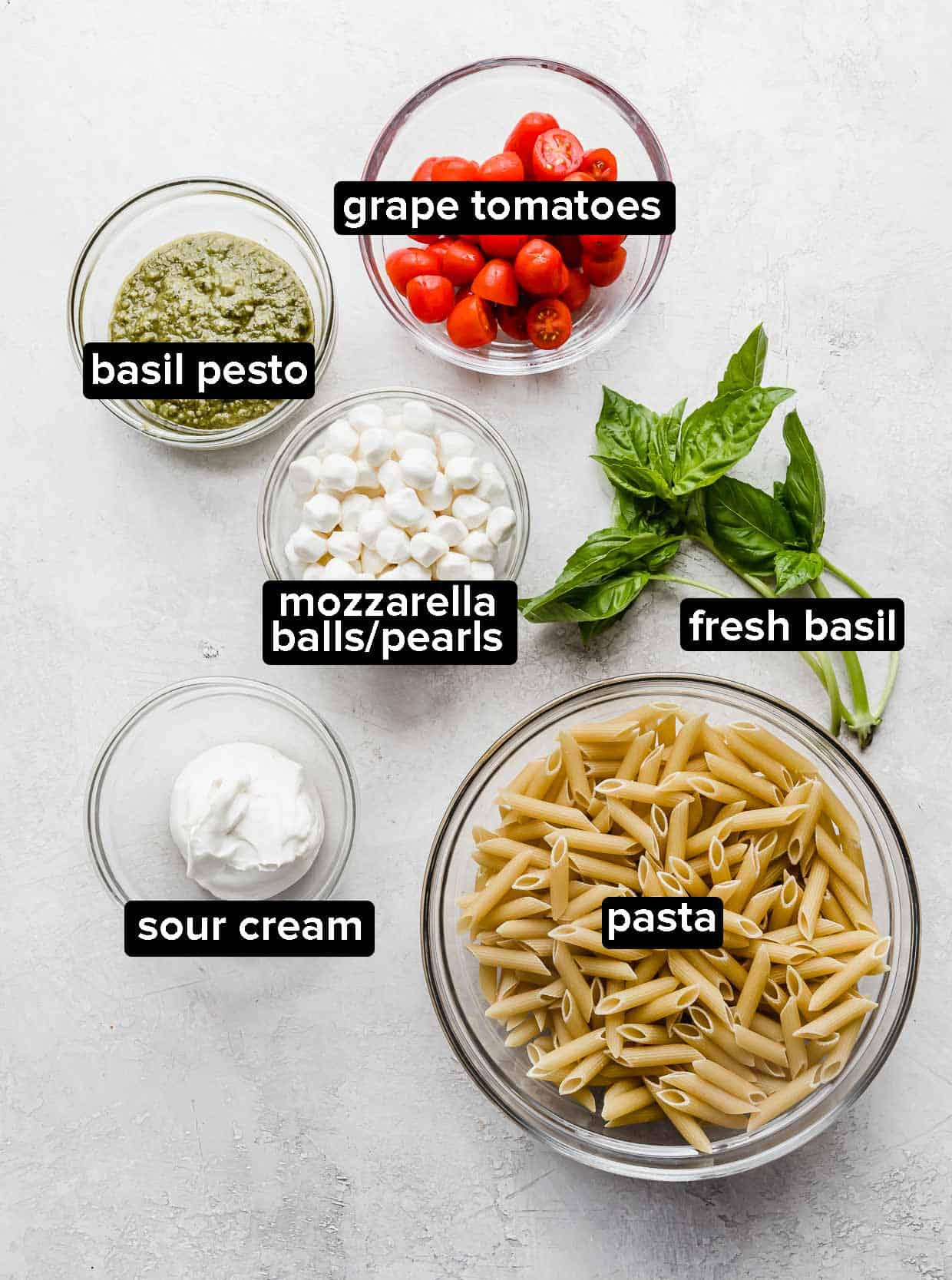 Ingredients used to make pesto pasta with tomatoes.