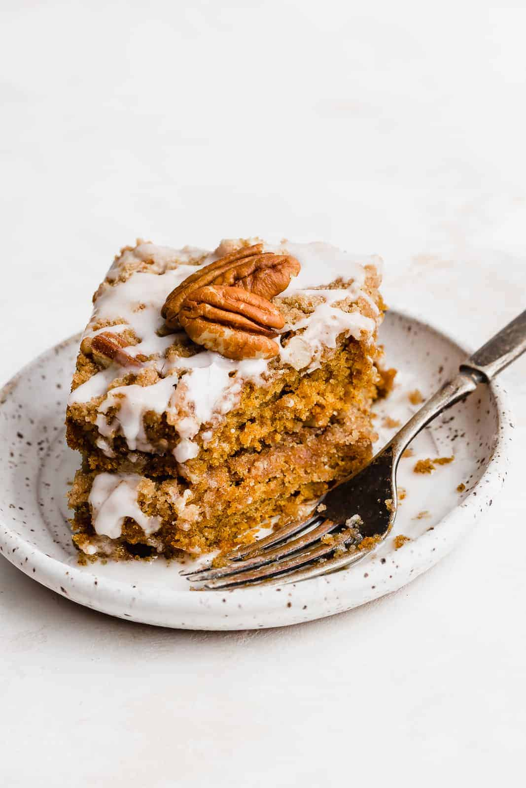 Pumpkin Coffee Cake on a white plate with a fork.
