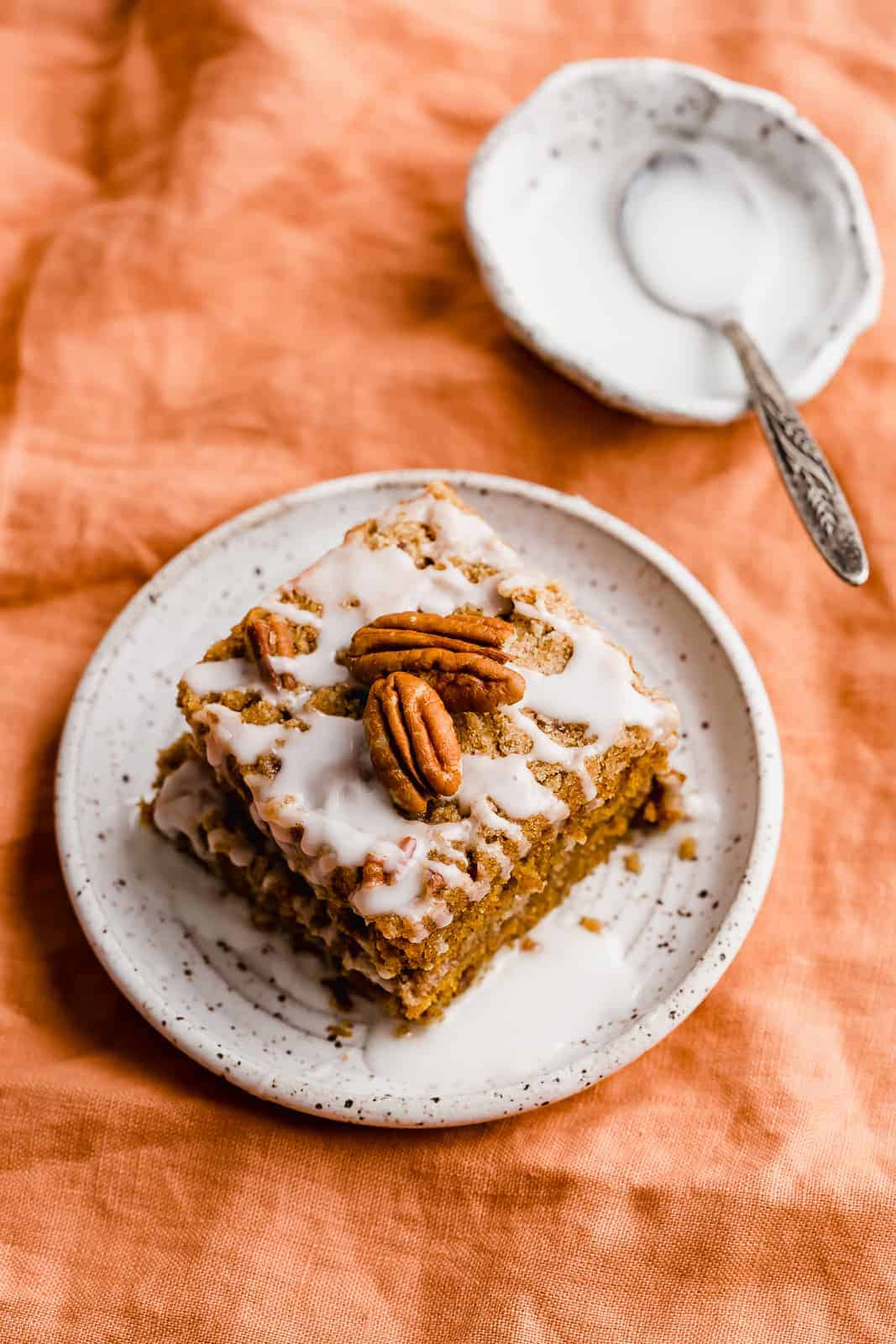 A slice of Pumpkin Coffee Cake on a white plate sitting on an orange linen napkin.