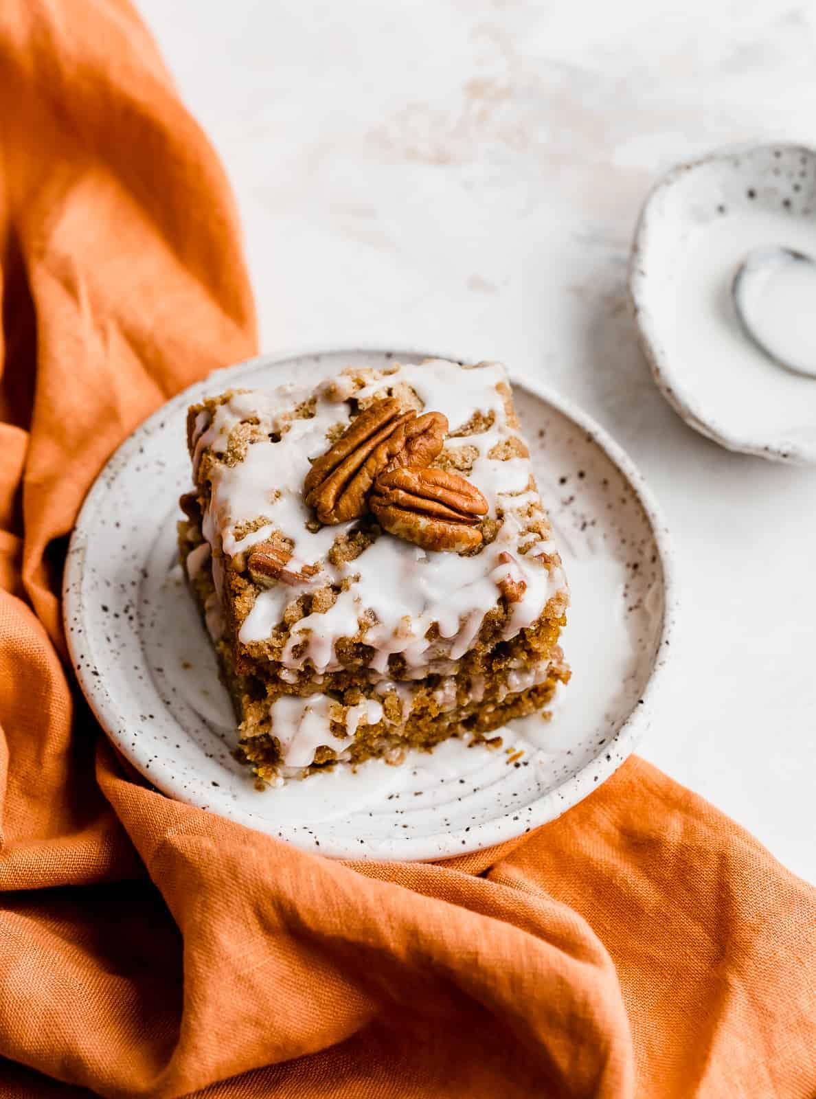 An orange napkin underneath a white plate with a slice of pumpkin coffee cake on top.