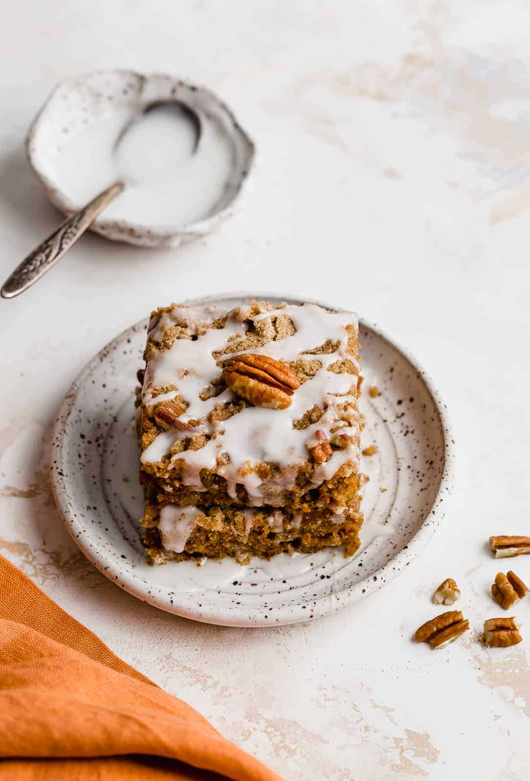 Pumpkin Coffee Cake with glaze, on white plate with chopped pecans next to the plate.