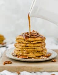 A stack of pumpkin pancakes with chopped pecans on top and syrup being drizzled over the stack.