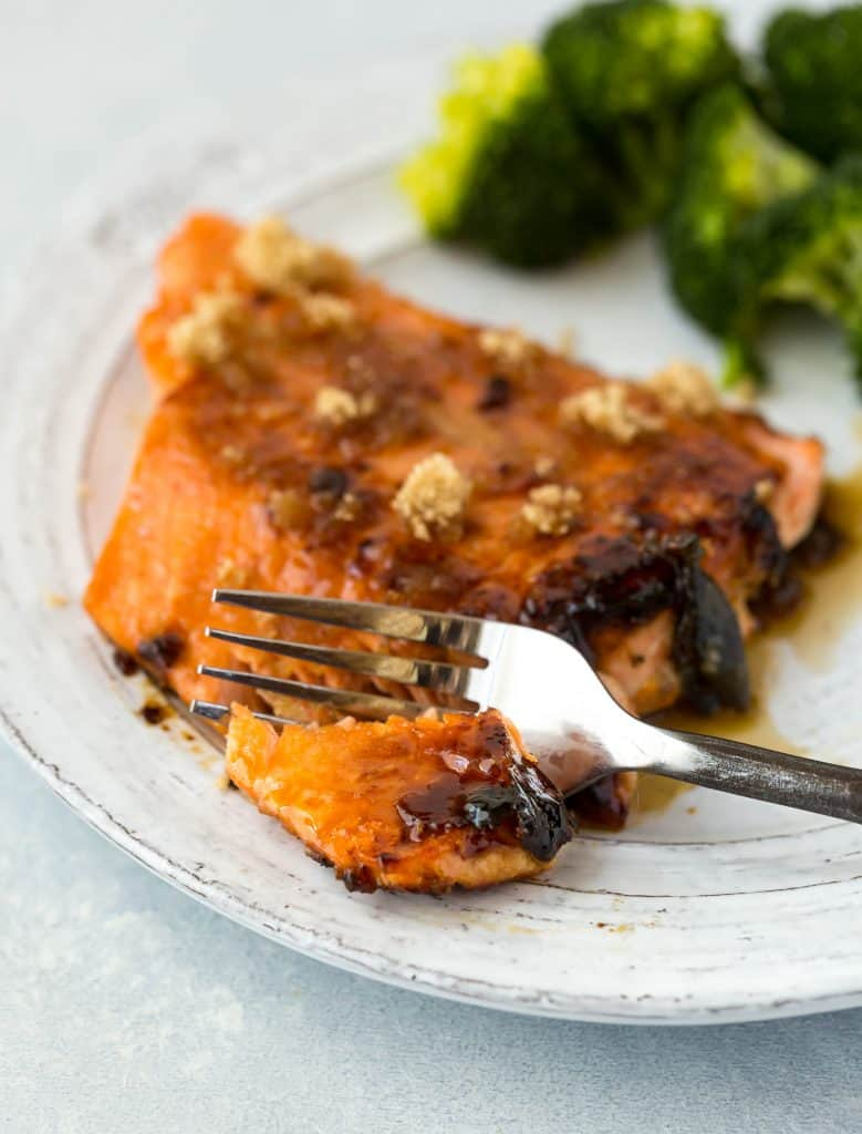 A close up of a fork cutting into a brown sugar crusted salmon fillet.