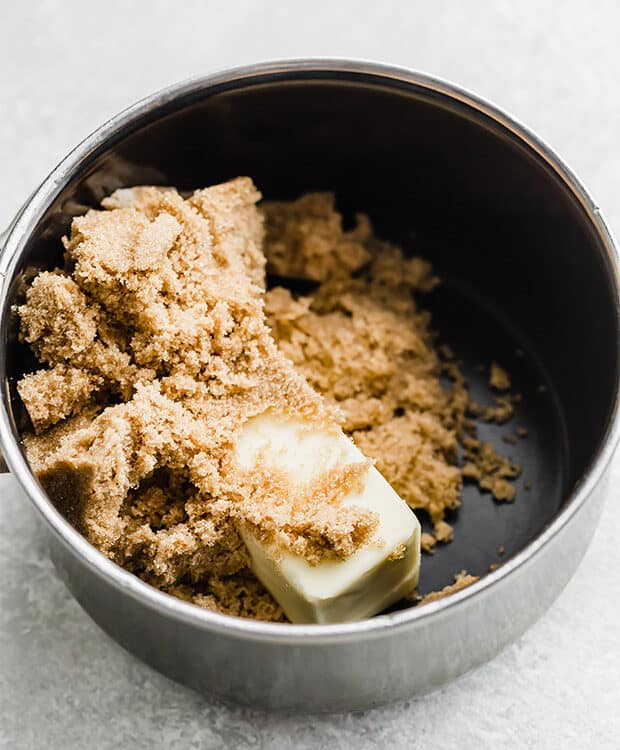 A saucepan with a cube of butter and brown sugar in it.