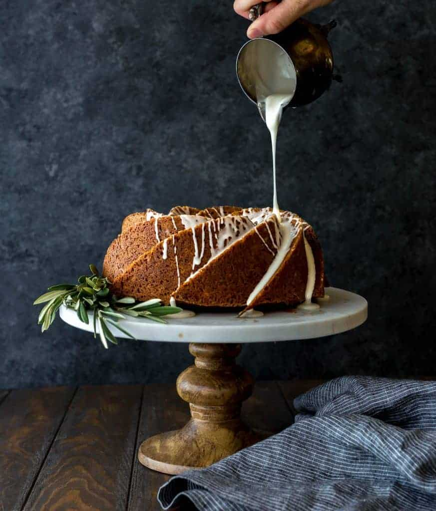 A beautiful gingerbread bundt cake on a cake stand, with olive branches laying at the base of the cake.