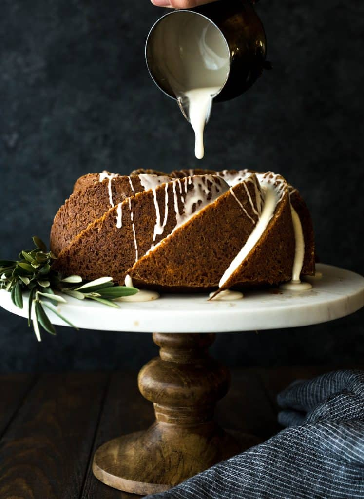 Gingerbread bundt cake sitting on a cake stand, with maple glaze slowly drizzling over the cake.
