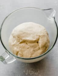 The best pizza dough recipe in a glass bowl, risen and ready to use.