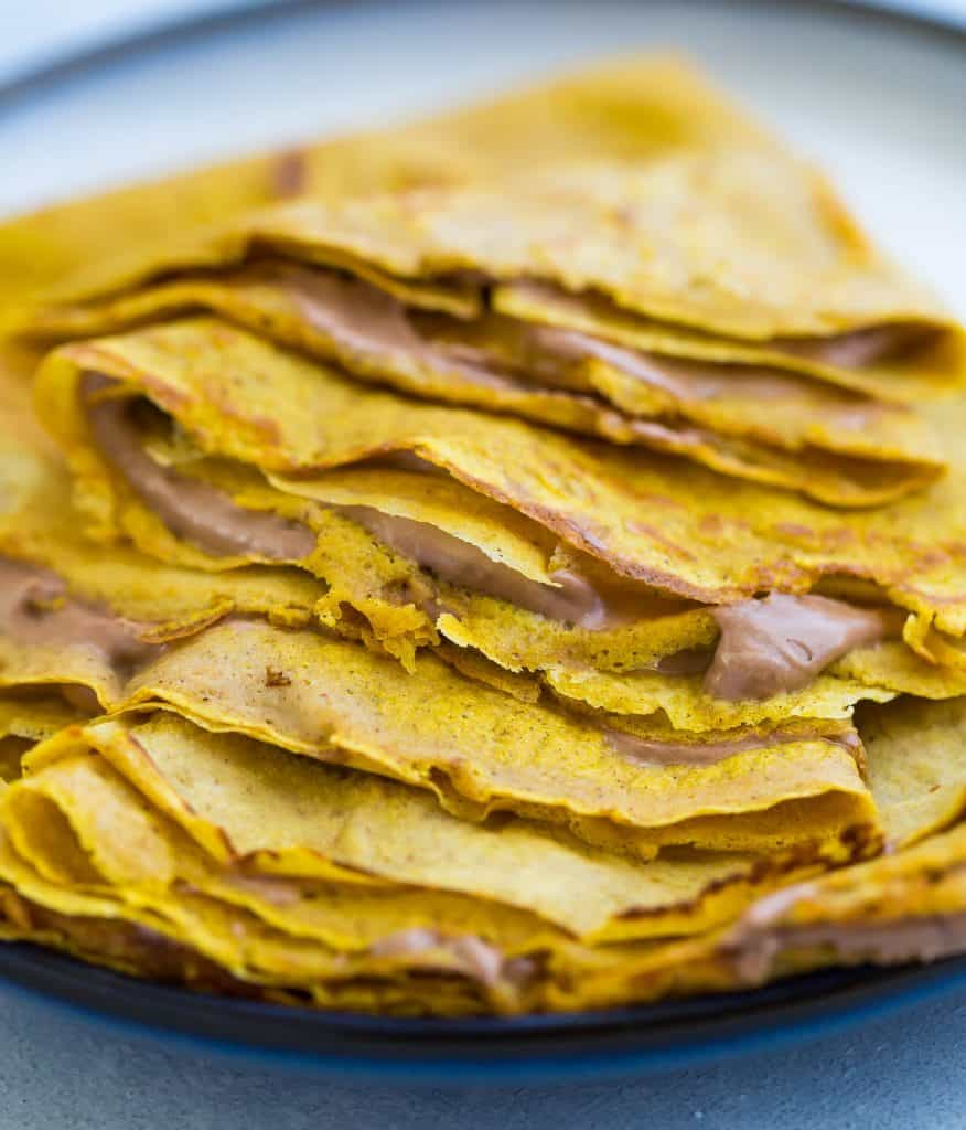 Pumpkin crepes loaded with whipped Nutella, gently sitting on a plate.