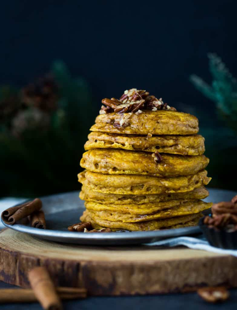 A stack of 6 pumpkin pancakes on a metal tin plate, with cinnamon brown butter syrup dripping down the sides of the pancakes.