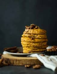 A stack of 6 pumpkin pancakes sitting on a metal tin, with cinnamon brown butter pecan syrup drizzling down the sides.
