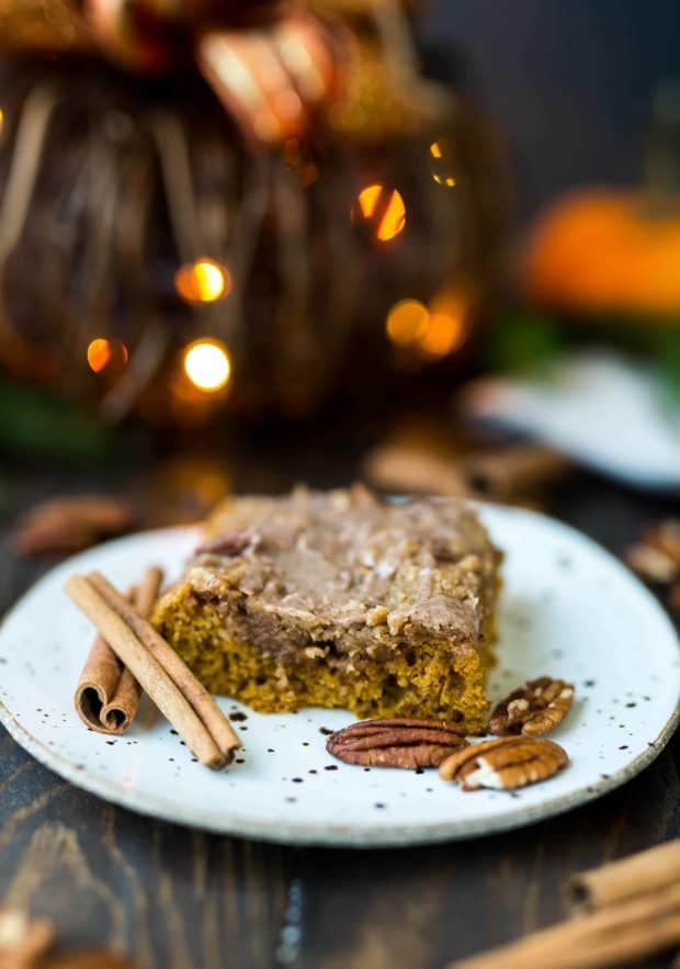 A slice of pumpkin cake surrounded by pecan halves and cinnamon sticks.