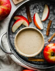 A bowl of caramel apple dip surrounded by cinnamon sticks and sliced apples.