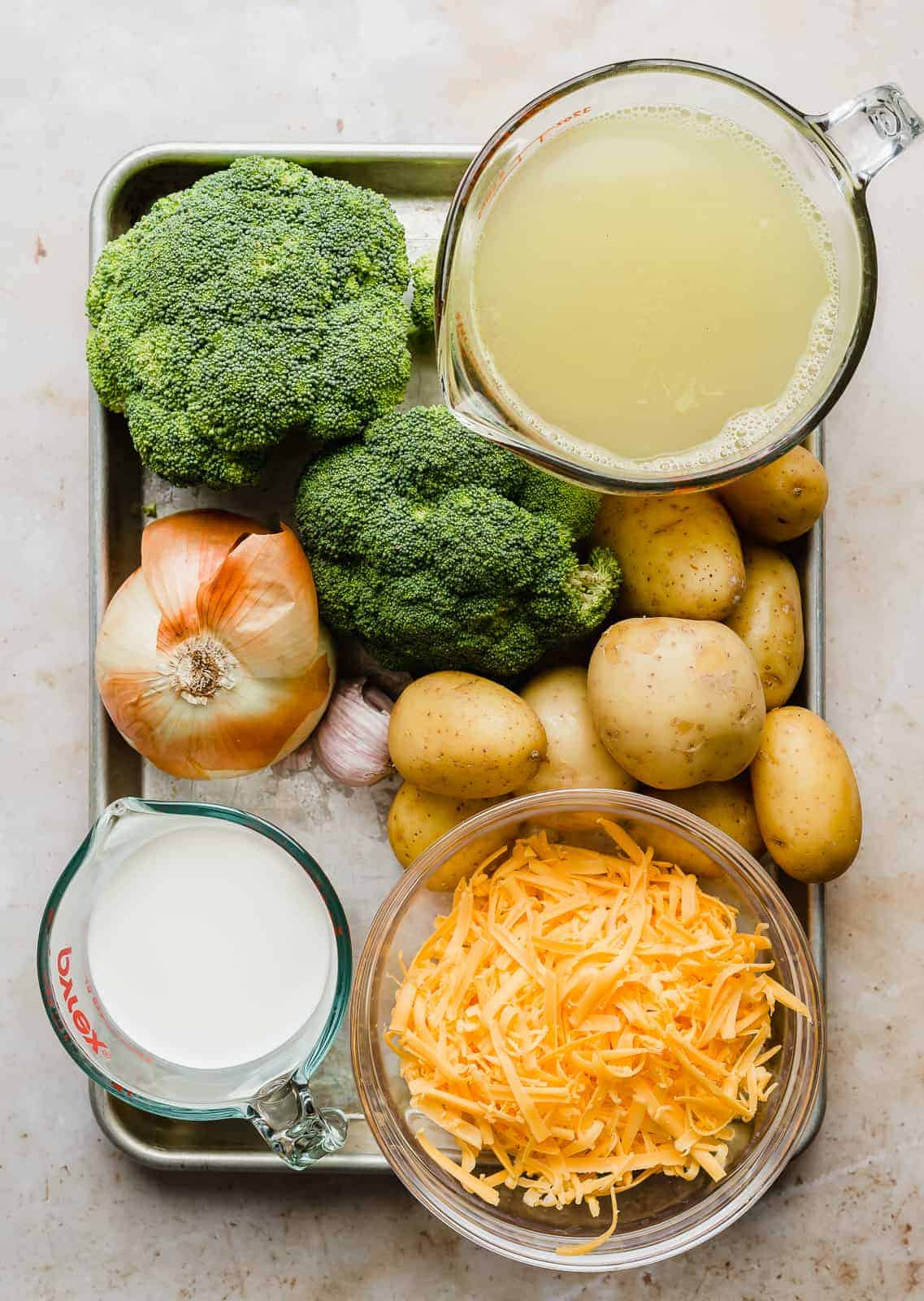 A baking sheet full of ingredients used to make Broccoli Potato Soup: cream, cheese, potatoes, chicken broth, broccoli.