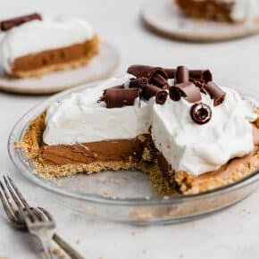 A French Silk Pie topped with whipped cream and homemade chocolate curls.
