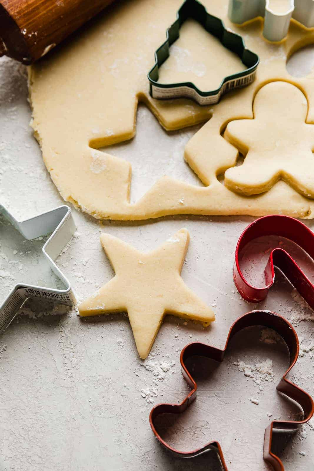 Sugar cookie dough rolled out and a star shape cookie cutter next to the dough.