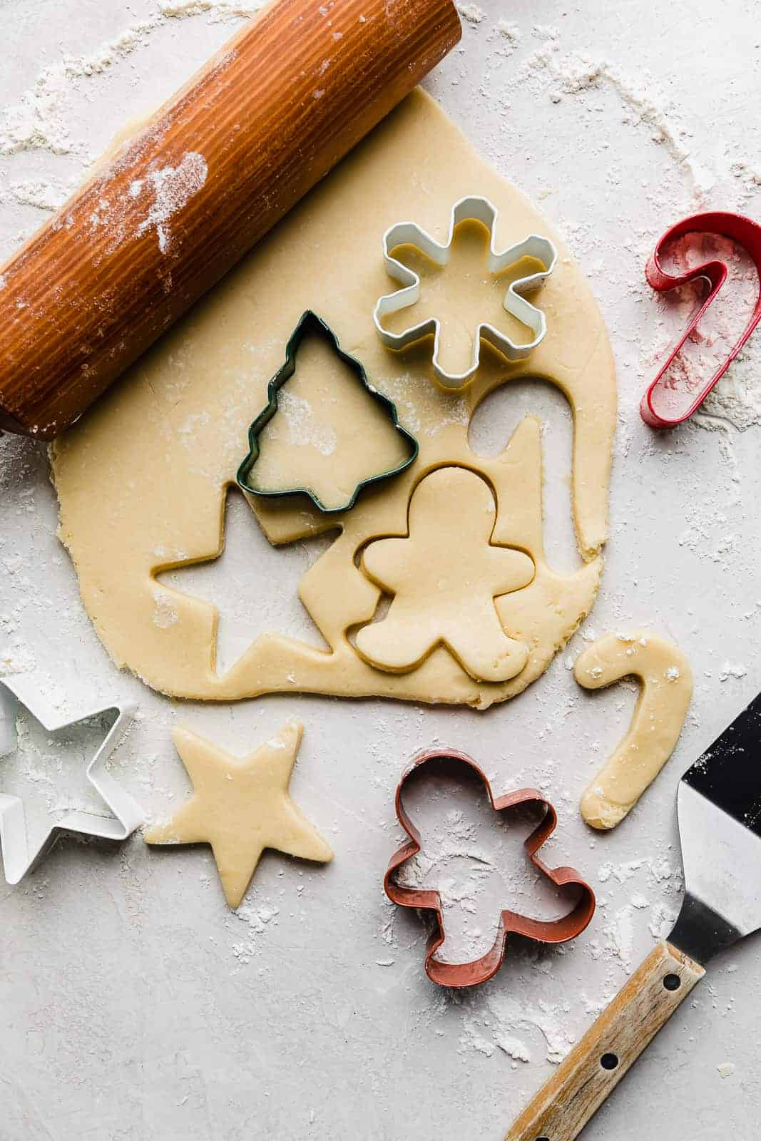 Rolled out sugar cookie dough with Christmas cookie cutters on top of the dough.