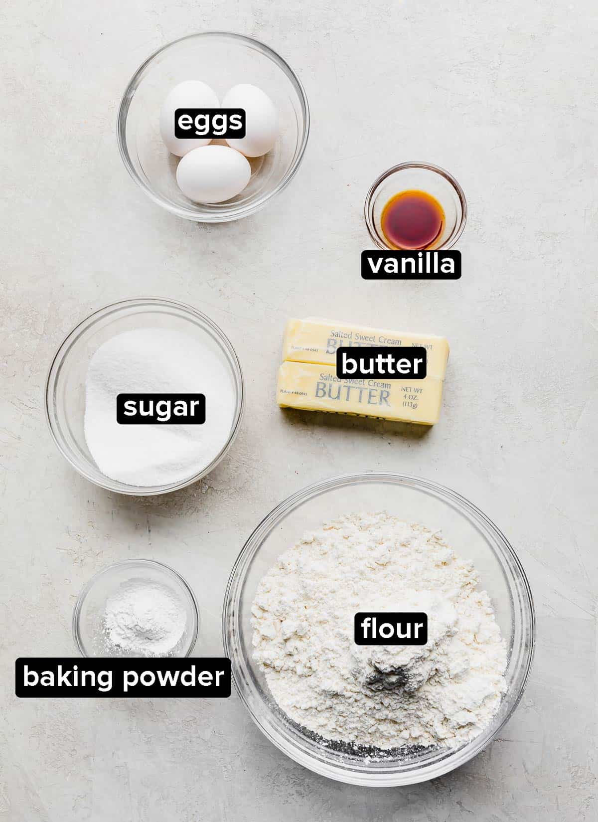 Ingredients used to make No Fail Sugar Cookies, on a gray background.