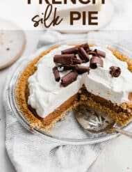 A French Silk Pie topped with whipped cream and chocolate curls.