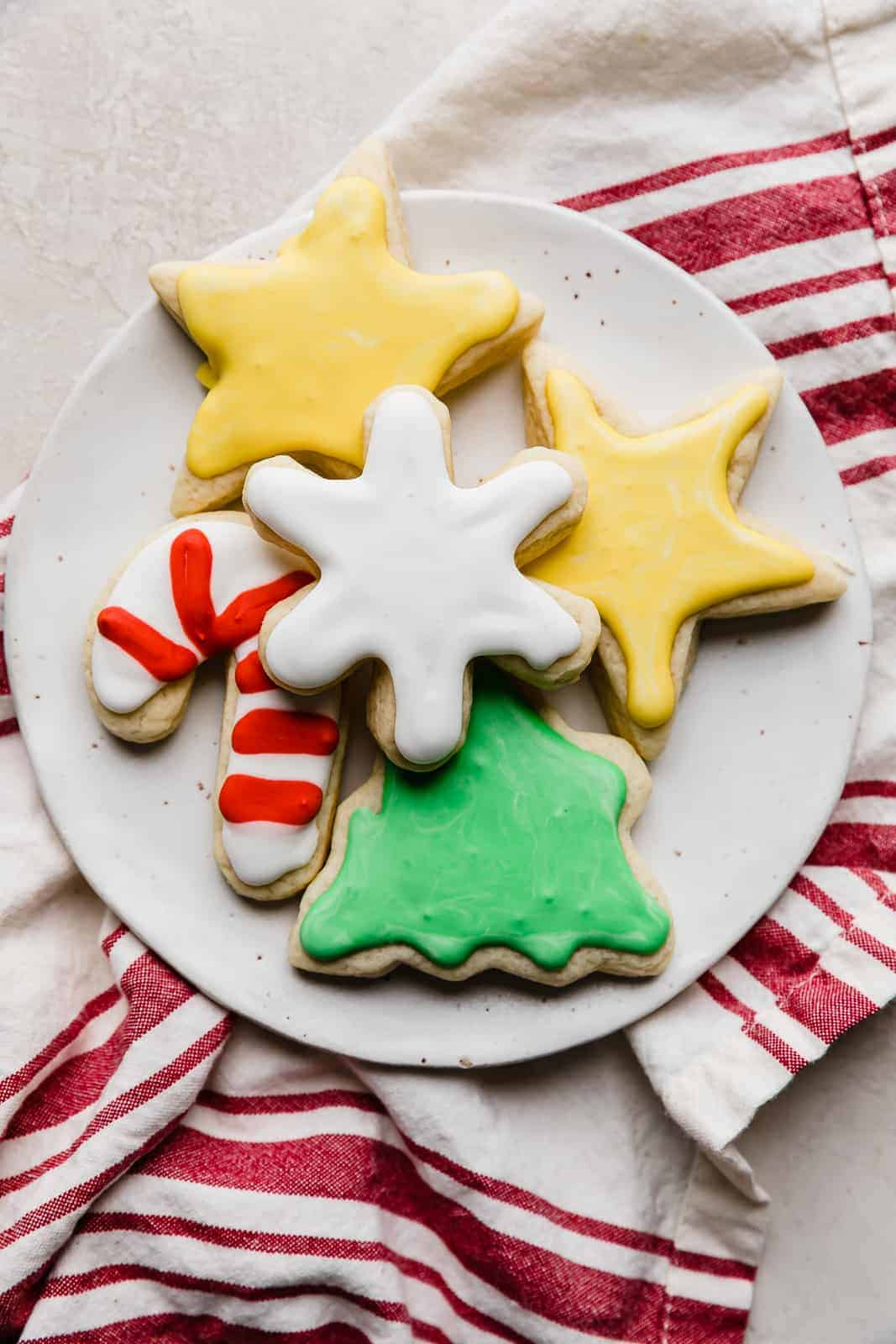 Christmas sugar cookies topped with royal icing on a white plate.
