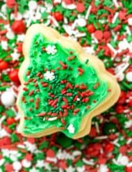 A never fail Christmas tree shaped sugar cookie on top a plate of sprinkles.