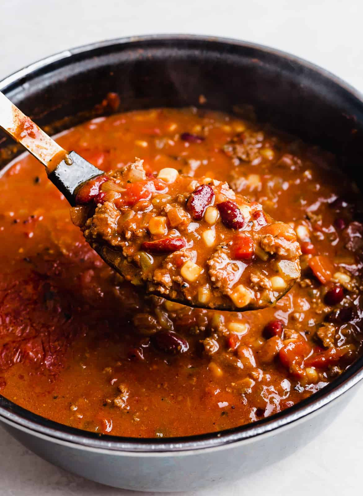 A large spoon scooping up taco soup from a pot.