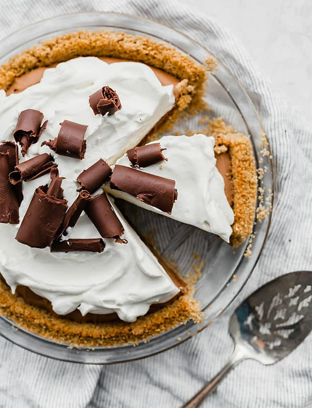 Overhead photo of a French silk pie, topped with freshly whipped cream and chocolate curls.