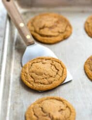 Soft gingersnap cookies on a baking sheet.