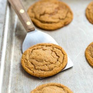 Soft gingersnap cookies on a baking sheet.