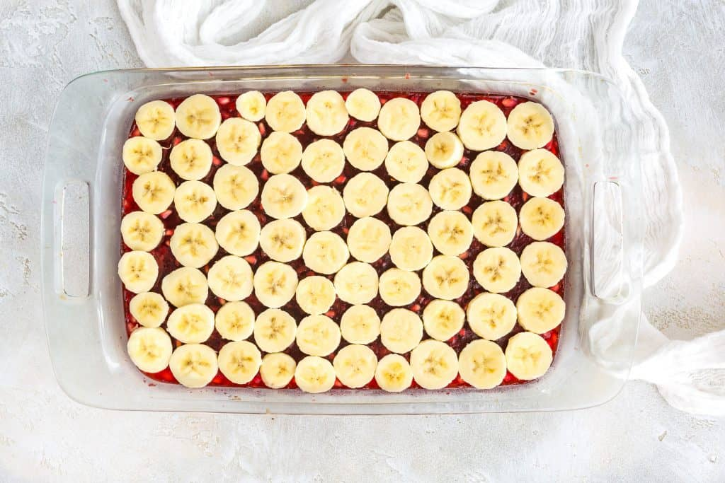Pomegranate Jell-O topped with sliced bananas.
