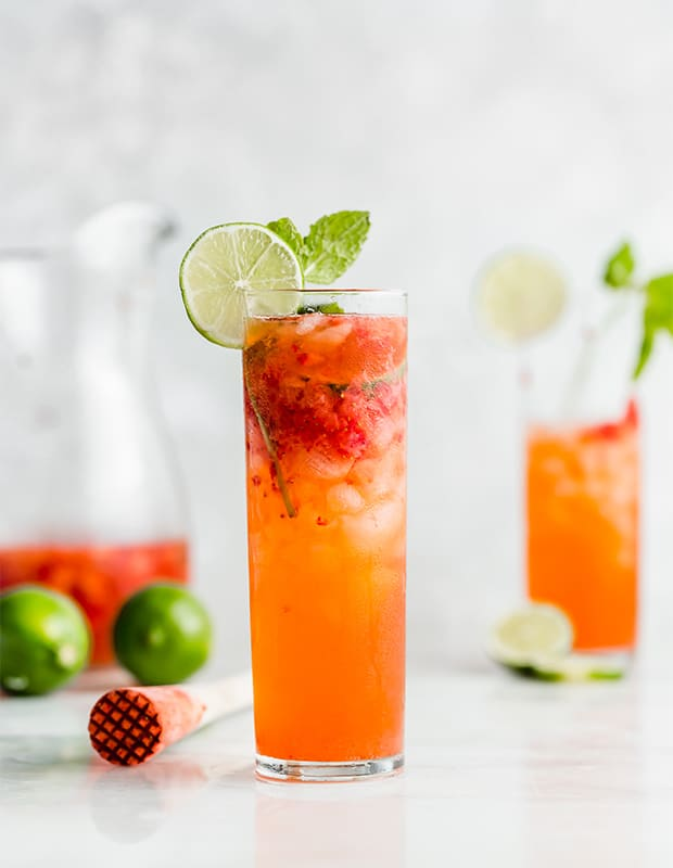 A mojito glass full of strawberry lime mojito drink.