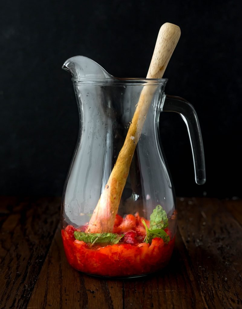 Glass pitcher with strawberries and mint leaves.