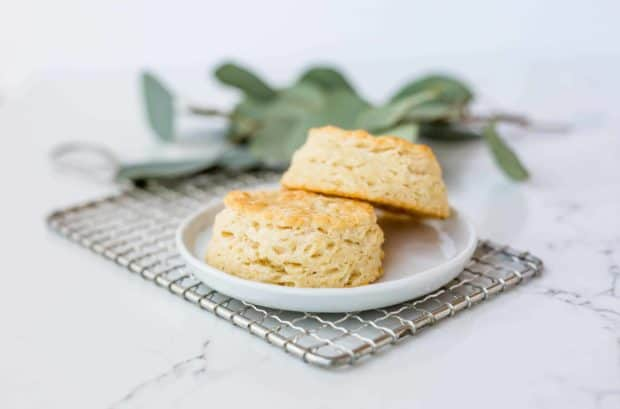 Two flakey buttermilk biscuits on a small white plate.